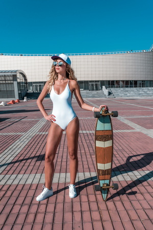Beautiful woman baseball cap, skate board, longboard, girl summer city. White bodysuit swimsuit glasses sneakers. Concept fashion style, new trend, weekend rest fresh air. Active sport and lifestyle