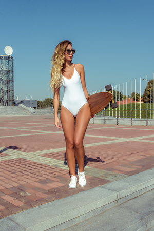 Beautiful woman long hair skate board, longboard, girl summer city. White bodysuit swimsuit glasses sneakers. Concept fashion style, new trend, weekend rest in fresh air. Active sport and lifestyle. Фото со стока