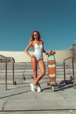 Beautiful woman skate board, longboard, girl in summer city. White bodysuit swimsuit glasses sneakers. Concept fashion style, new trend, weekend rest in fresh air. Active sport and lifestyle.