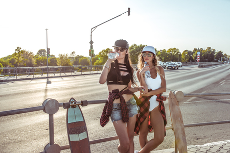 Two girls girlfriends students drink water in summer city, skate boards, swimsuit shorts. Resting long hair tanned figure. Background road cars. Fashion style, modern lifestyle. Free space for text Фото со стока