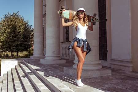 Girl summer in the city, posing with a board, longboard skate, sunglasses baseball cap white bodysuit jeans. Fashion style, free space for text. Tanned skin has long hair.