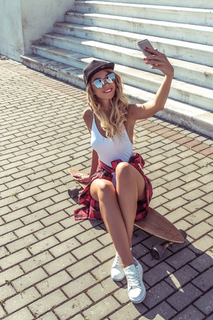 A girl in summer city, photographs on phone, makes selfie, online call Internet application, a board, a longboard skate, sunglasses, a white body. Fashion style. Tanned skin has long hair. Фото со стока