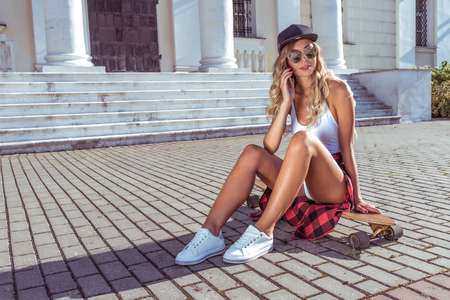 Woman in summer city, phone rings, online call Internet application, board, longboard skate, sunglasses white body. Fashion style. Tanned skin has long hair. Free space. Фото со стока