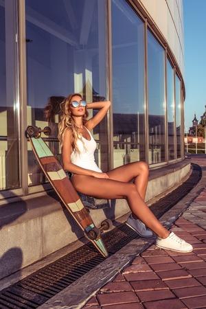 Woman in summer in city, sunbathes in city, board, longboard skate, sunglasses white bodysuit. Fashion style. Tanned skin has long hair. Fashion style modern lifestyle. Фото со стока