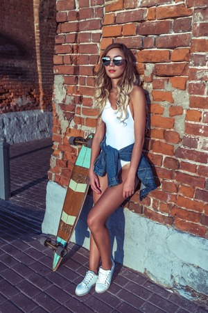 Stylish girl in summer in city, stands at brick wall anticipation of friends and girlfriends with longboard board, fashion lifestyle, modern expression art. Long hair tanned woman fitness figure. Фото со стока