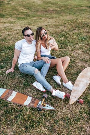 Young couple man woman sit grass summer city weekend, happy ones smiling joking having fun. Skateboard board longboard, casual wear, love relationship concept. Date meeting loving friends