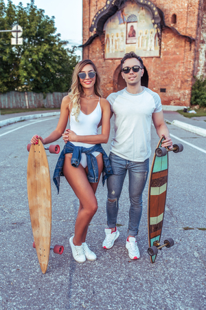 A young couple a man and a woman walk in the summer in city at the weekend, the happy ones are smiling joking and having fun. Skateboard board longboard, casual wear, love relationship concept. Фото со стока