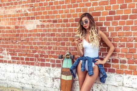 A girl with glasses summer city, writes message phone, reads news line social networks. Concept fashion style modern lifestyle of young people. Free space. Online internet application concept