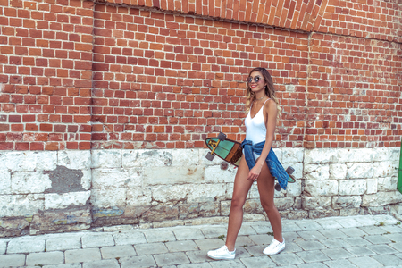 Happy girl walks summer city, smiling rests weekend, in hands skateboard board. Free space for text. Emotions joy fun, background wall. Tanned fitness figure athlete on longboard
