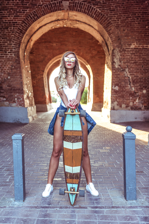 Stylish girl summer city, stands with longboard board, background arch bricks, fashion lifestyle, modern expression art. Long hair tanned woman fitness figure. Background denim sneakers tan tile