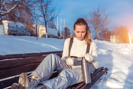 The girl on bench in overalls in winter on street, background snow drifts. In hands of a tumbler with hot tea coffee. Holidays at the weekend in ski resort. Warm sweater mittens clothes Фото со стока