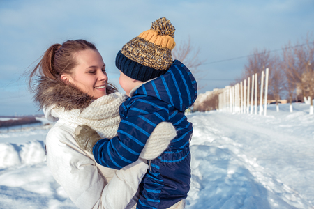 A young and happy mother holds the child in her arms, smiles and rejoices. Street winter fresh air, a boy of 3 years. Winter warm clothing, weekend rest concept at a winter resort.