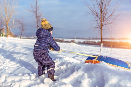 A little boy of 3-5 years old, pulls an inflatable toy tubing for skiing from slide in winter outside, background snowdrifts idea playing with a child in winter on hill. Free space text. Фото со стока