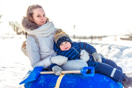 Mom with a boy son 3 years old, in the winter in a pair on a hill, an inflatable toy for skiing tubing, fresh air. Holiday weekend city park. Play fun laugh laugh. Фото со стока