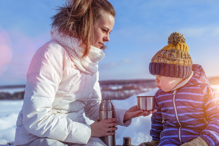Mom with a boy son 4 years old, in the winter in a pair in the fresh air. Rest at the weekend resort, on the bench, a tumbler with tea and soup. The boy is blowing on a mug, cool hot tea.