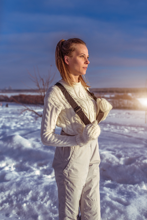 A woman in a white jumpsuit in winter outside, background is snow drifts, looking into distance, a warm sweater and white mittens. The concept of outdoor recreation at weekend outside winter