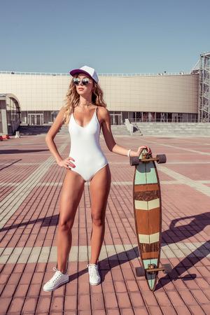 Woman posing skateboard, summer city, outdoor recreation walking, white bodysuit swimsuit. Fashion lifestyle modern youth. Tanned figure sunglasses long hair. A woman sunbathes city weekend Фото со стока