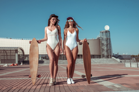 Two girlfriends girl stand skateboard, in summer city, rest fresh air walk, white body swimsuit. Fashion lifestyle modern youth. Tanned figure sunglasses, long hair. Women weekend sunbathe in city