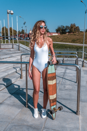 Girl skateboard, summer in city, outdoor recreation, walking, white body swimsuit. Fashion lifestyle, modern youth. Tanned figure sunglasses, long hair. A woman sunbathes city weekend