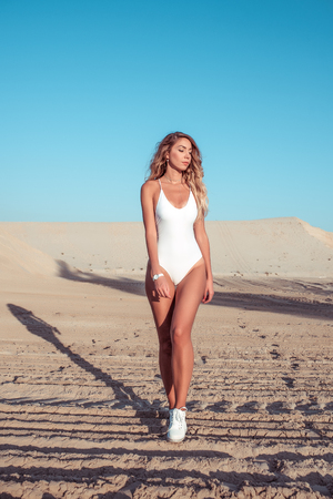 The girl walks on the sandy beach, rest walks in body of swimsuits, the sea at the ocean lake tan. Fashion lifestyle, modern youth. Tanned figure. Active lifestyle of a woman. Фото со стока