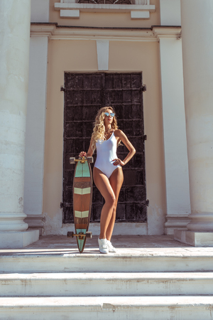 Girl skateboard, summer city, posing background door columns. White bodysuit swimsuit, long hair longboard for riding. Fashion lifestyle of the youth. Concept ideas for weekend getaway