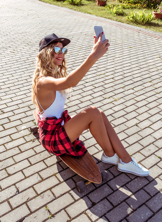 A skateboard girl, summer city, takes selfie of herself, online call Internet. Happy smiling, long hair longboard for riding. Fashion lifestyle of youth. Concept ideas for weekend getaway