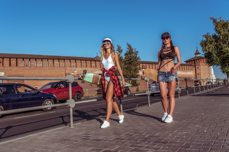 Two girls girlfriends skateboard, summer city, walking along road, background of car, long hair for longboarding. Fashion is lifestyle of youth. Concept ideas for weekend getaway. Free space.