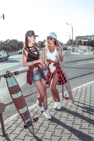 Two girls girlfriends skateboard, summer city stand road, background machine, drink water from bottle, longboard skating. Fashion lifestyle youth. Concept ideas weekend getaway. They talk smiling. Фото со стока