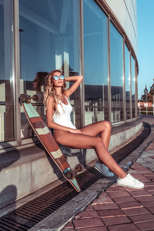 Beautiful young girl sunbathes summer city, background building glass windows, skateboard, white body swimsuit, sunglasses. Long legs tanned figure. Emotions relaxation, comfort enjoyment