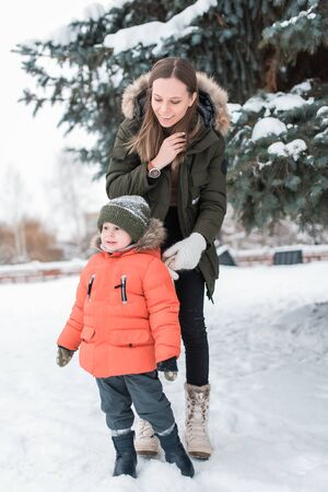 Young woman mother, in winter on street, walks with young son a boy of 3-4 years. Warm jacket winter clothing. Rest on the weekend walk in the fresh air, background snow tree and snowdrifts. Фото со стока
