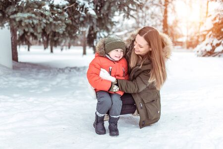 Young woman mother winter street, plays with her young son boy 3 years. Happy smiling, weighing up, laughing rejoicing. Warm jacket winter clothing. Rest weekend walk fresh air, background snow tree