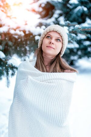 A portrait close-up winter girl background snow Christmas trees. White warm winter hat, large long woolen plaid sweater. Rest at weekend in nature, in cold weather at the resort. Happy smiles.