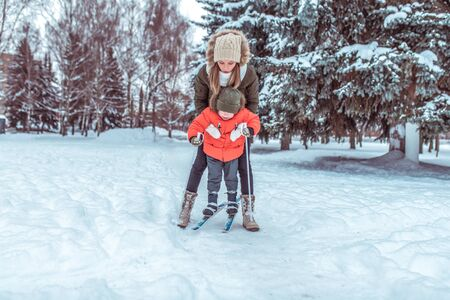 Young mother insures supports child childrens skis, little boy son of 4 years. Winter forest park, background snow drifts trees. Concept taking care child, first steps sports fitness training Фото со стока