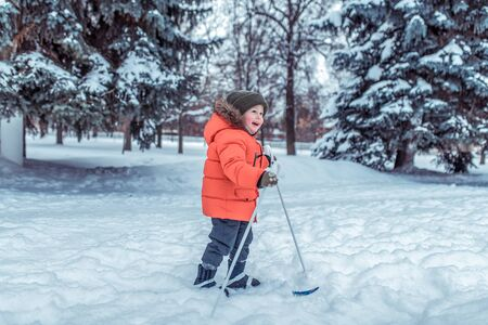Little boy 3-4 years old, winter childrens skis, happy smiling plays, having fun, active image of children. Background snow drifts trees. Free space. The idea of happy childhood fresh air in nature