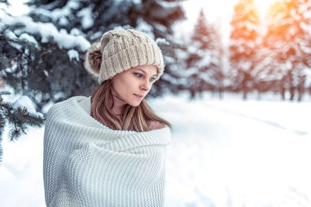 Closeup portrait winter woman background snow and Christmas trees. White warm winter hat, large long woolen plaid sweater. Rest weekend in nature, in cold weather resort. Free space for text. Фото со стока