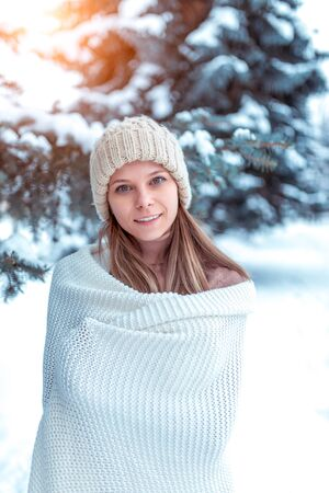 The girl in winter stands smiling rejoices, rest in the fresh air in the forest. White sweater plaid, warm knitted hat. Emotions of joy fun winter vacation enjoyment. Background snow drifts trees. Фото со стока
