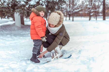 Young mother woman straightens childrens skis little boy son 3 years. Winter forest park, background snow drifts. Concept taking care child, first steps sports training active lifestyle.
