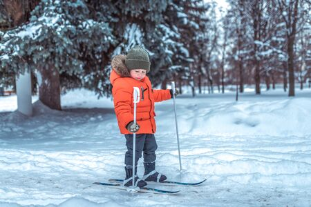 Little boy is 3-4 years old, winter on childrens skis, first steps skis, active image of children. Background snow drifts trees. Free space. The idea of happy childhood in the fresh air in nature Фото со стока