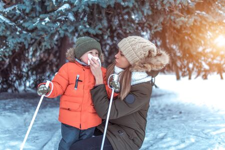 A woman mom wipes her nose with handkerchief, snot napkin small child, caring child during cold season in winter outside, background snow drifts of Christmas tree. A little boy is 3-4 years old Фото со стока