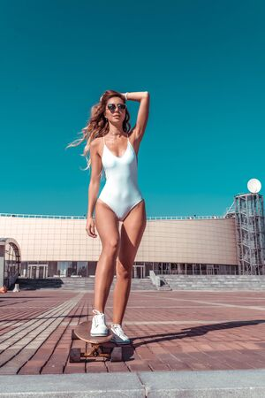 Beautiful and athletic girl riding on board, in the summer in the city lifestyle, fashion is a modern trend. Tanned figure, fitness. The concept of a weekend holiday. Stockfoto