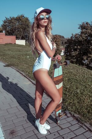 Beautiful woman, sporty girl in summer in city. Lifestyle, fashion. Modern trend. Tanned figure, fitness. The concept of a weekend holiday. Long legs slim figure, baseball cap glasses.