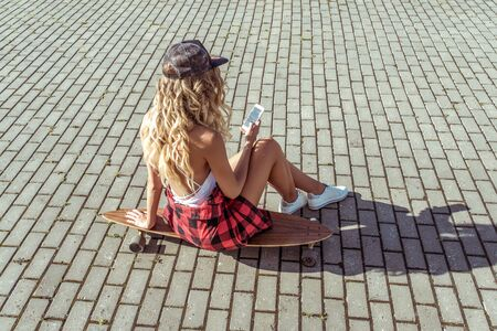 Girl blonde with long hair, summer city sits skateboard, reads message application online, social networks. Fashion lifestyle, modern idea concept trends. Tanned figure. Background paving tile road Фото со стока