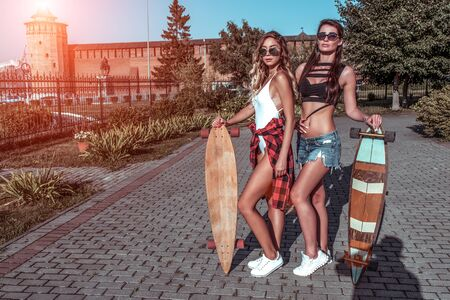 Two girls girlfriends, standing background of city trees, skateboard, beautiful and tanned figure. Concept best friends girlfriend. Weekend rest, free space modern clothes, fashion lifestyle, trend. Фото со стока