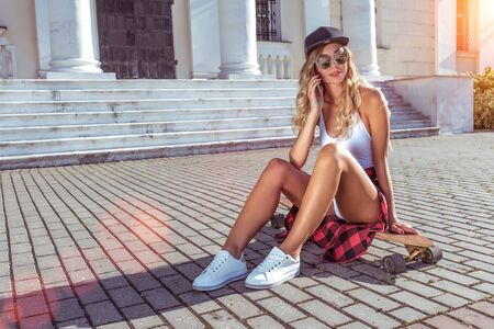 A girl baseball cap makes telephone call, summer skateboard sits in city, online internet application listens voice message, social networks. Fashion lifestyle, modern idea concept trends. Free space Фото со стока