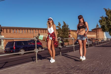 Two girls girlfriends walking city, background road pavement skateboard cars, beautiful and tanned figures. Concept best friends girlfriend. Weekend rest, modern clothes, fashion lifestyle, trend Фото со стока