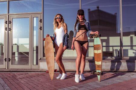 Beautiful girls girlfriends, two women posing skateboard, longboard, background window glass building. The concept fashion lifestyle, trendy clothes. Denim swimwear baseball cap sunglasses
