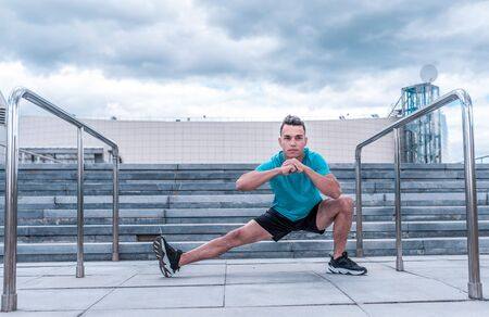 Male athlete, in the summer in the city, stretching the muscles before jogging, fitness training, sportswear, concentration and focus on the goal. Stair background and blue sky. Stockfoto