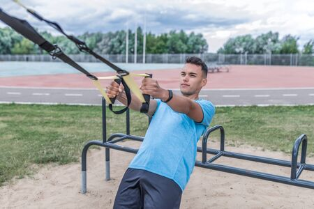 young sports man summer city, pulls up and wring out on his hinges, straps horizontal bar, healthy lifestyle fitness workout, workout concept strength motivation success. Lifestyle young generation Banco de Imagens