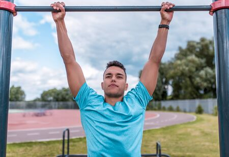 Athletic man in summer in city, pulls up on bar, a healthy lifestyle fitness workout, workout in fresh air. The concept of strength and motivation for success. Lifestyle of young generation