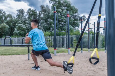 Young guy male athlete doing lunges look from back, squats city summer sports ground, webbing loops, leg muscle training, active lifestyle health sport concept full-length sportswear, fitness watches Stockfoto
